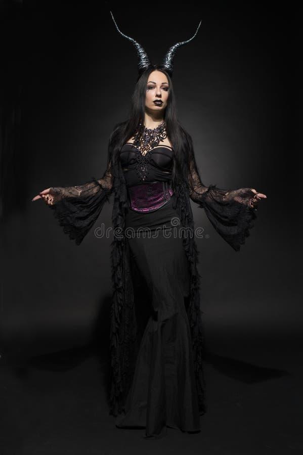 Jeune femme dans le costume noir d'imagination photographie stock libre de droits