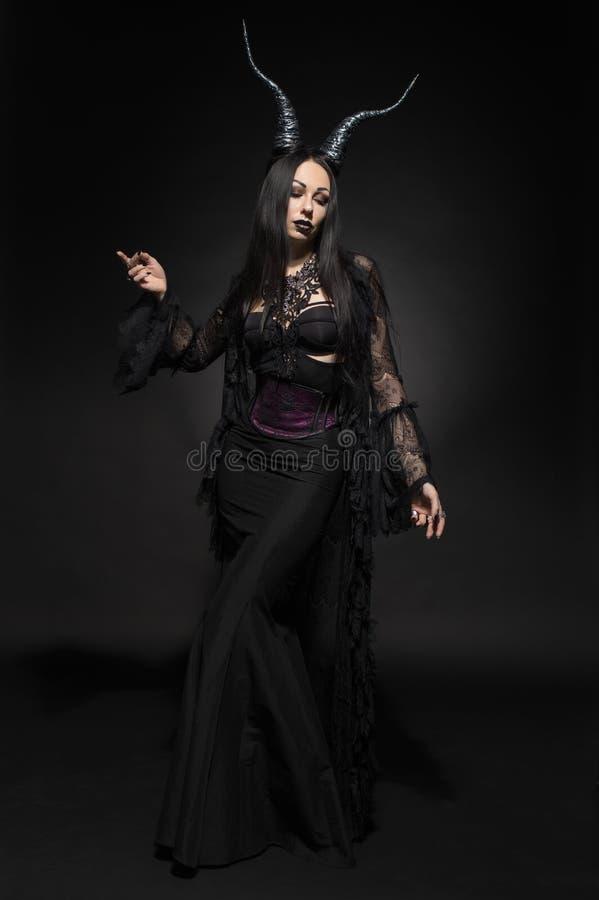 Jeune femme dans le costume noir d'imagination photo libre de droits