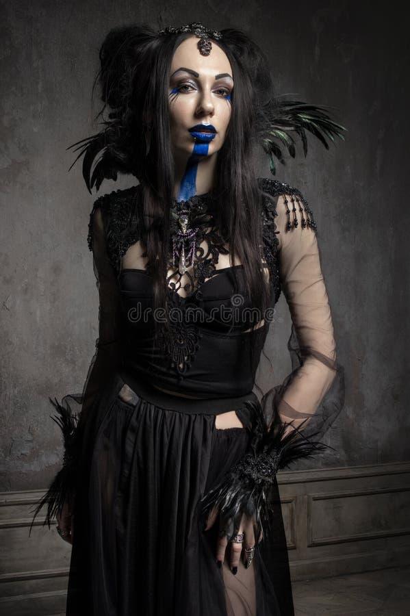 Jeune femme dans le costume noir d'imagination photographie stock