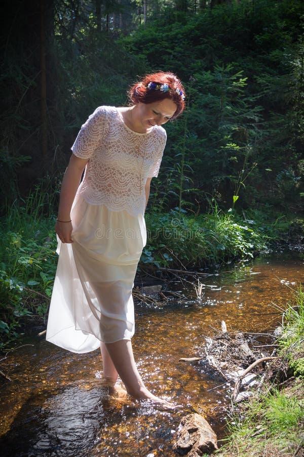 Jeune femme dans le courant de forêt photographie stock