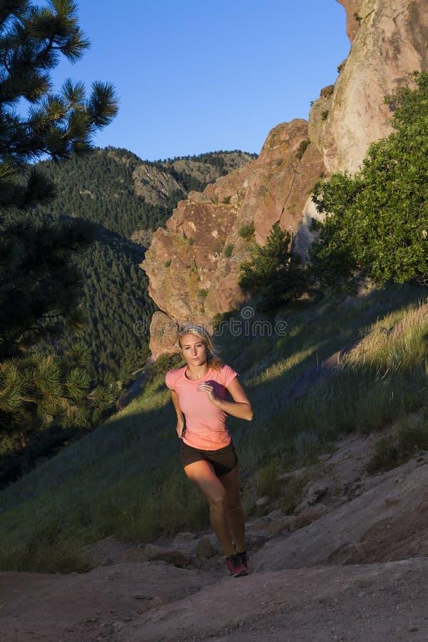 Jeune femme dans le dessus rose courant la colline raide avec la vue de montagne image libre de droits