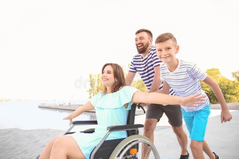 Jeune femme dans le fauteuil roulant avec sa famille marchant dehors image libre de droits