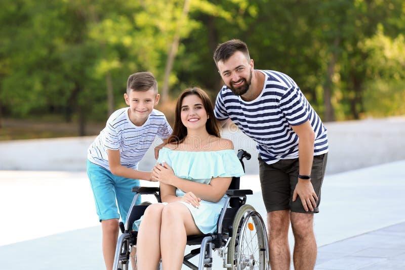 Jeune femme dans le fauteuil roulant avec sa famille marchant dehors photographie stock libre de droits