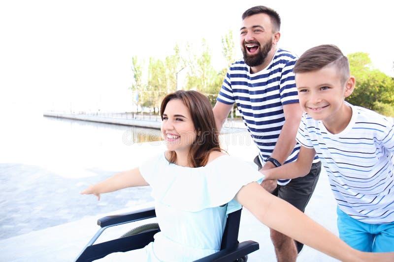 Jeune femme dans le fauteuil roulant avec sa famille marchant dehors photos stock