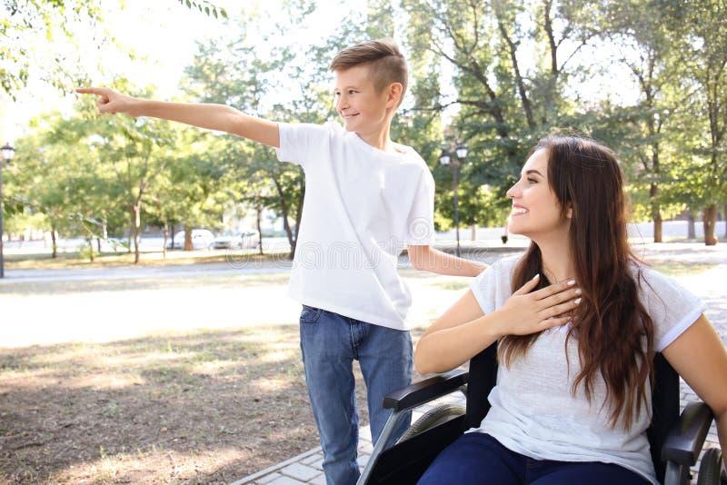 Jeune femme dans le fauteuil roulant avec son fils marchant dehors photo stock