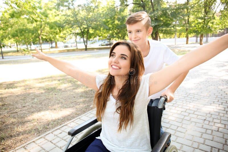 Jeune femme dans le fauteuil roulant avec son fils marchant dehors photos stock