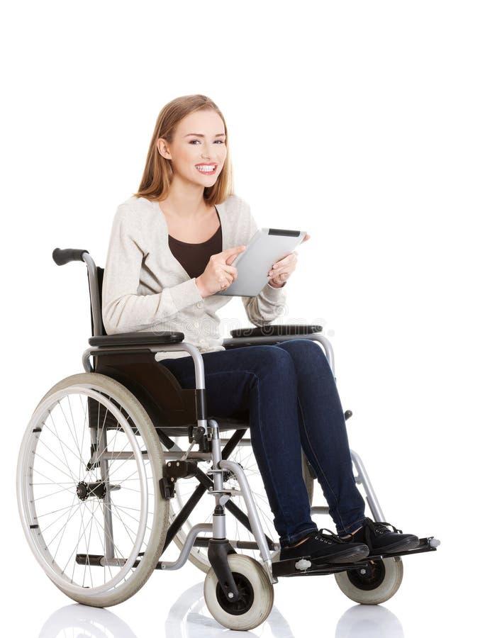 Jeune femme dans le fauteuil roulant tenant un comprimé photo stock
