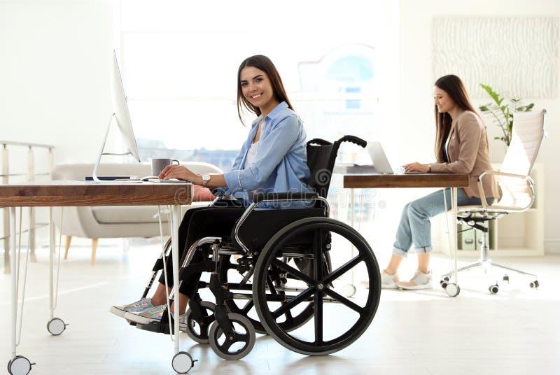Jeune femme dans le fauteuil roulant utilisant l'ordinateur photos stock