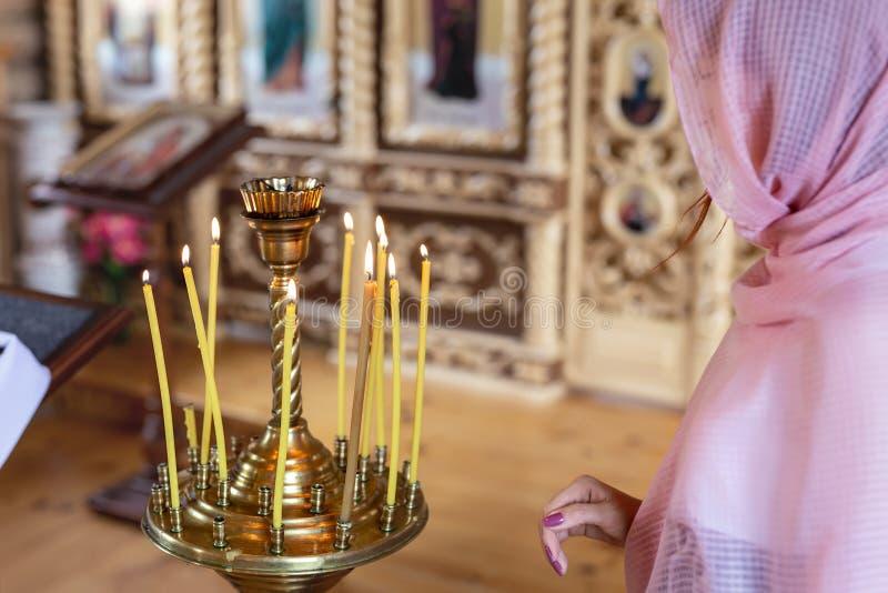 Jeune femme dans le foulard rose priant près des bougies à l'église en bois Dieu de culte de personne féminine dans le temple photo stock