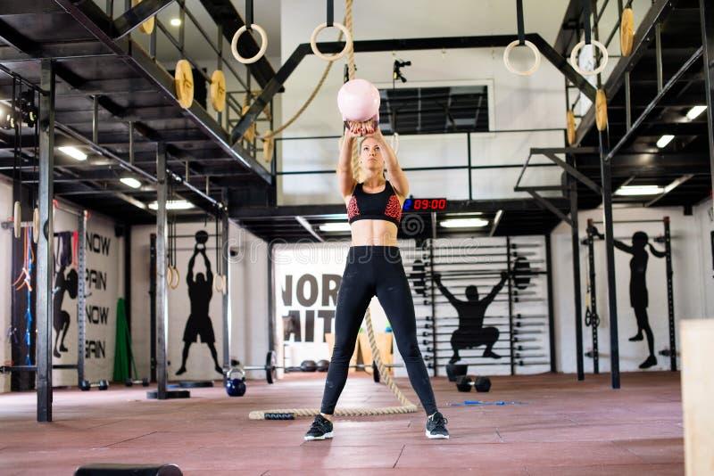 Jeune femme dans le gymnase, exercice avec le kettlebell images stock