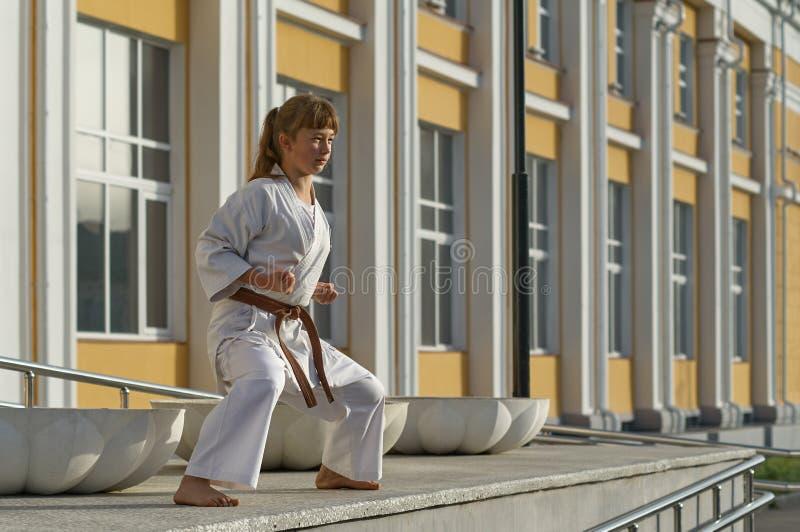 Jeune femme dans le kimono faisant l'exercice formel de karaté image stock