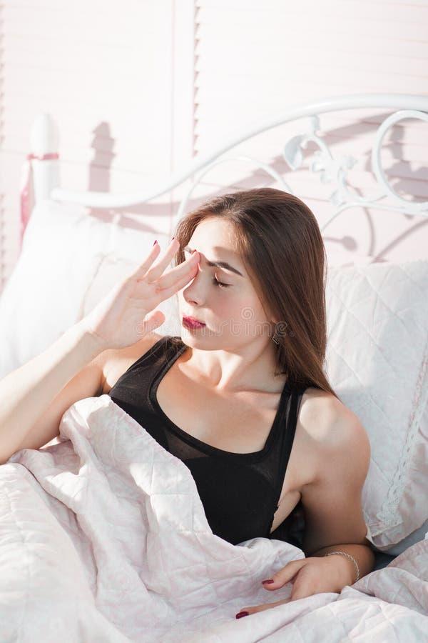 Jeune femme dans le lit avec le portrait de mal de tête images libres de droits