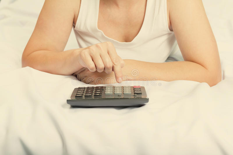 Jeune femme dans le lit avec une calculatrice Budget de famille Crédit, photos stock