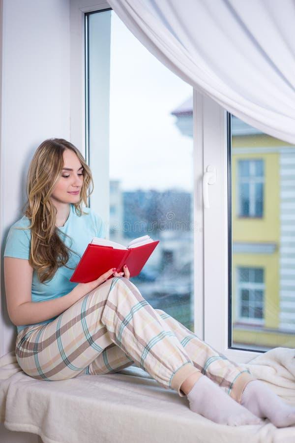 Jeune femme dans le livre de lecture de pyjamas par la fenêtre photo libre de droits