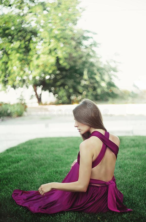Jeune femme dans le long sitteng de robe sur une herbe images libres de droits