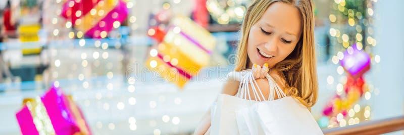 Jeune femme dans le mail de Noël avec des achats de Noël BANNIÈRE de remises d'achats de nuit de Noël d'achat de beauté, LONG FOR image stock