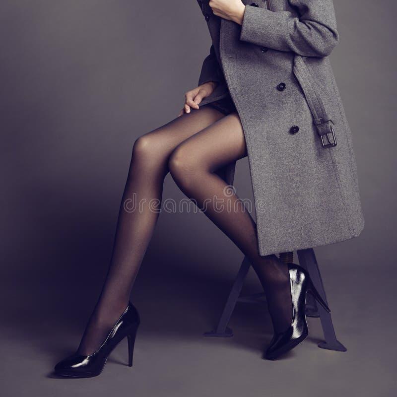 Jeune femme dans le manteau avec de beaux pieds image stock