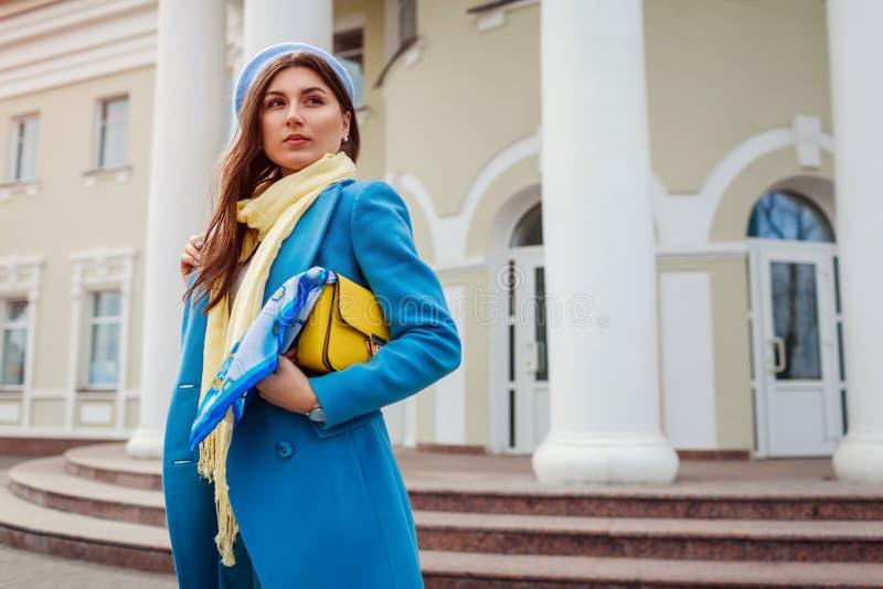 Jeune femme dans le manteau bleu à la mode marchant dans la ville tenant le sac à main élégant Vêtements et accessoires femelles  photos libres de droits