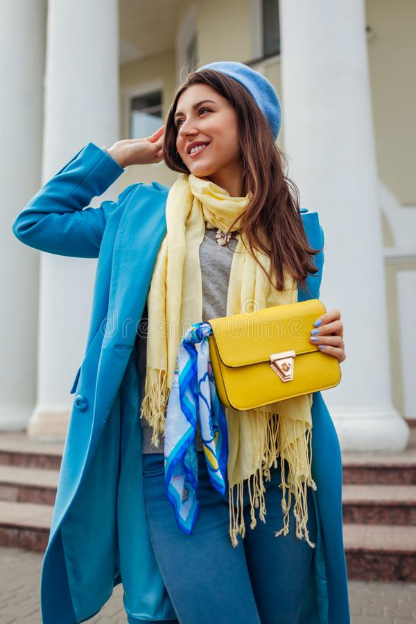 Jeune femme dans le manteau bleu à la mode marchant dans la ville tenant le sac à main élégant Vêtements et accessoires femelles  image libre de droits