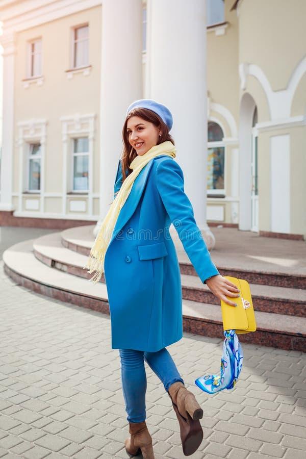 Jeune femme dans le manteau bleu à la mode marchant dans la ville tenant le sac à main élégant Vêtements et accessoires femelles  images libres de droits
