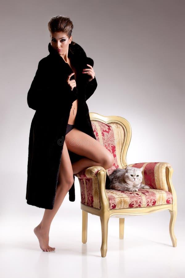 Jeune femme dans le manteau de fourrure et la Cat On Armchair photo libre de droits