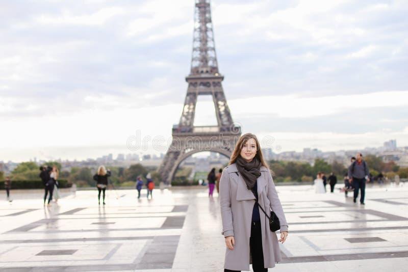 Jeune femme dans le manteau gris tenant Tour Eiffel proche à Paris image stock