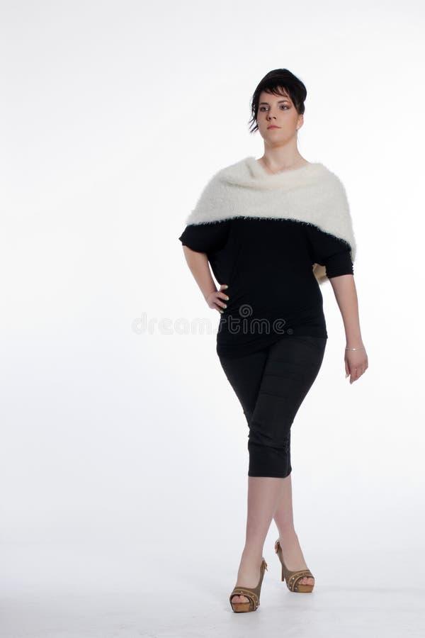 Jeune femme dans le noir avec le collier blanc de fourrure image stock