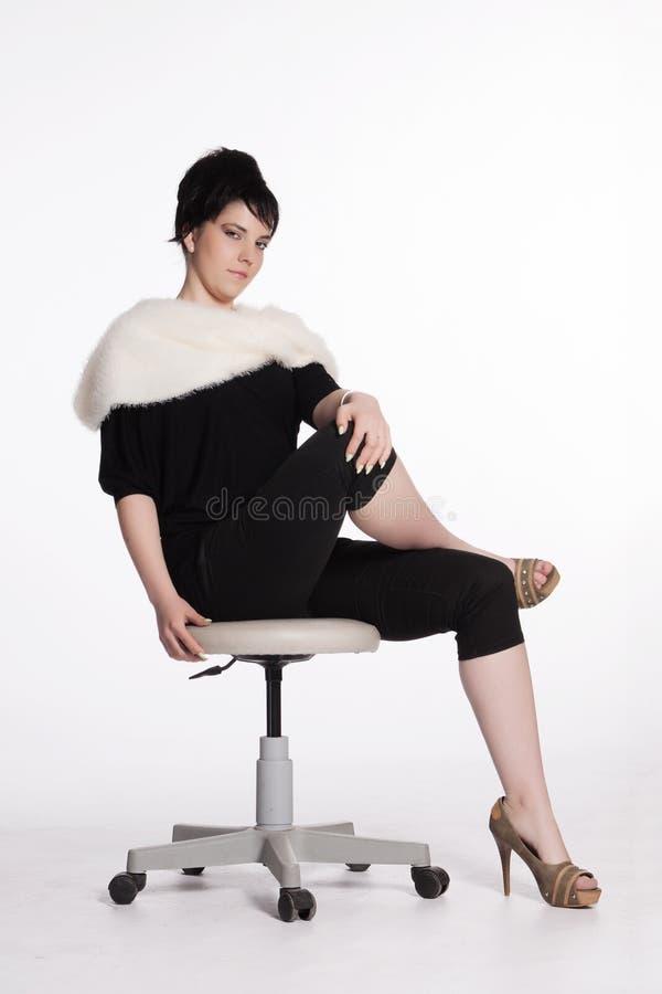 Jeune femme dans le noir avec le collier blanc de fourrure photo libre de droits
