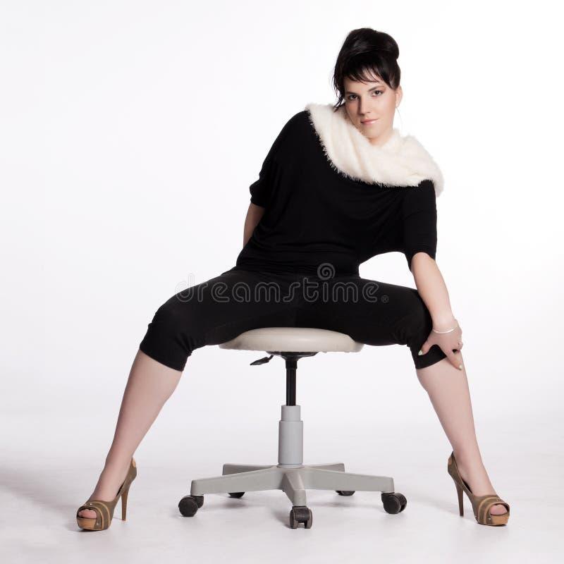Jeune femme dans le noir avec le collier blanc de fourrure photo stock