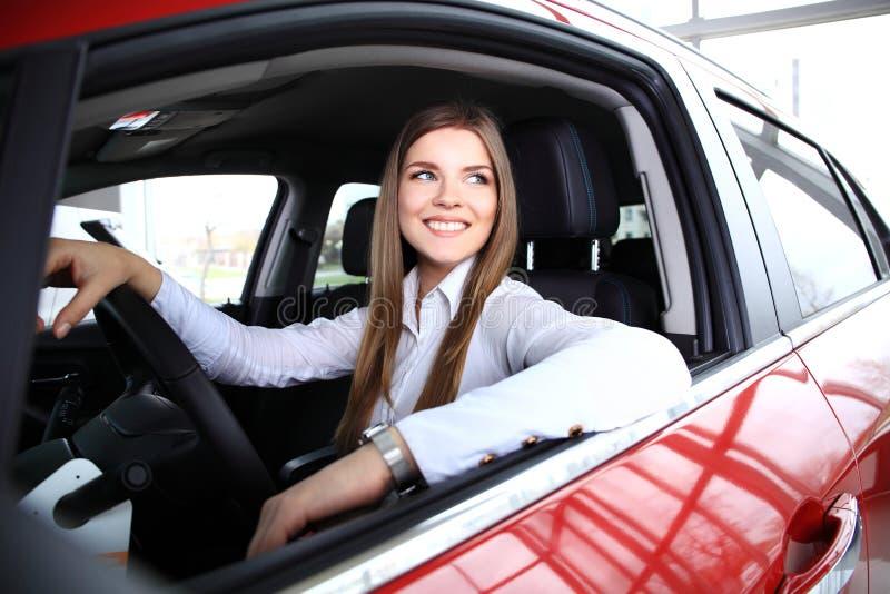 Jeune femme dans le nouveau sourire de voiture photographie stock