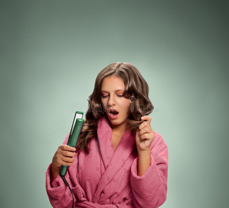 Jeune femme dans le peignoir tenant le fer de cheveux photo libre de droits