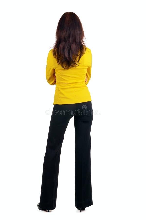 Jeune femme dans le procès jaune regardant le mur. photo stock