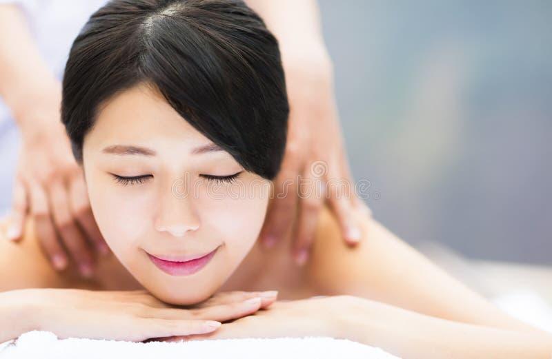 Jeune femme dans le salon de station thermale obtenant le massage photographie stock