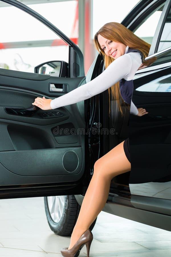 Jeune femme dans le siège de l'automobile au concessionnaire automobile photo stock