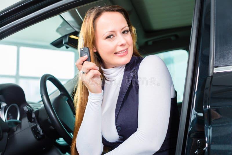 Jeune femme dans le siège de l'automobile au concessionnaire automobile images libres de droits