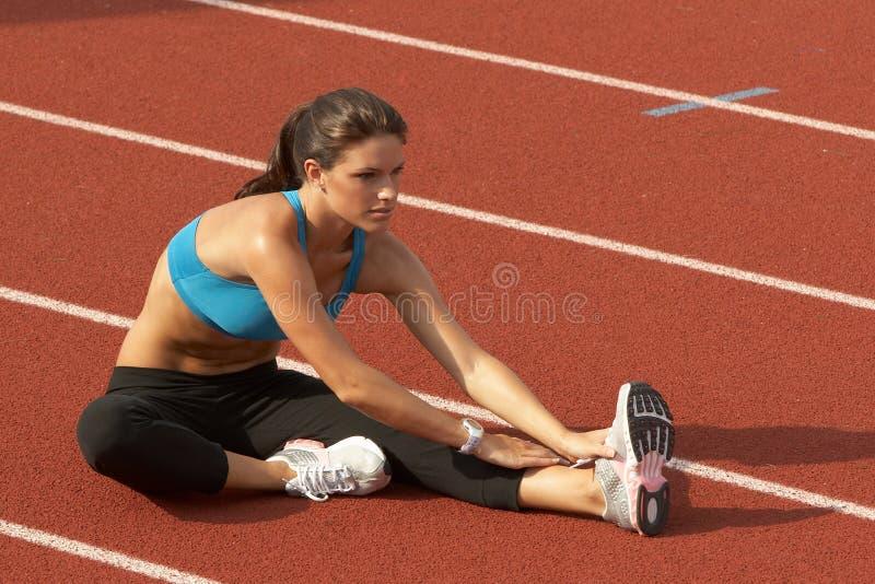 Jeune femme dans le soutien-gorge de sports étirant la patte sur la piste photos libres de droits