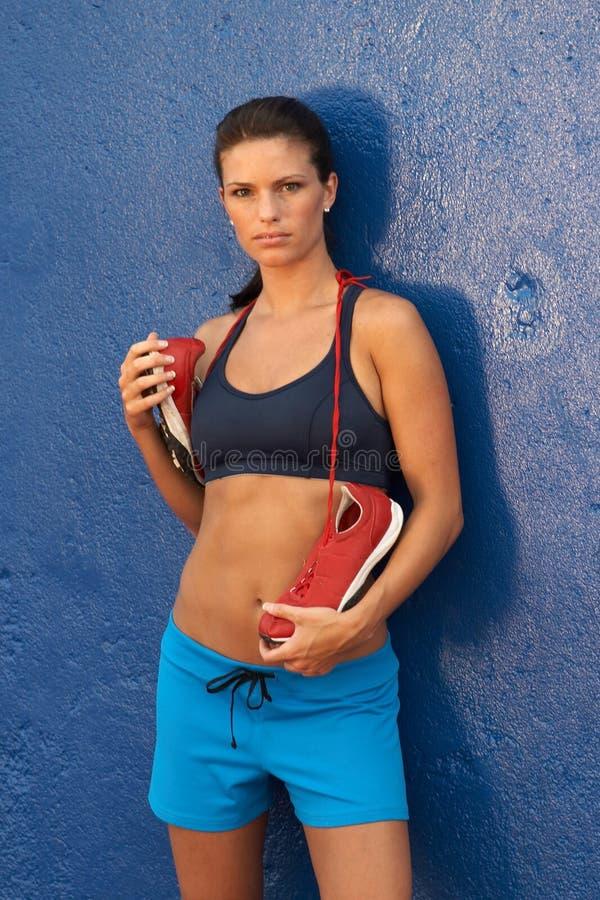 Jeune femme dans le soutien-gorge de sports et des chaussures de course se penchant contre le mur image stock