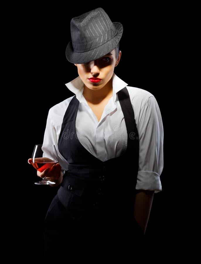 Jeune femme dans le style viril avec le verre d'eau-de-vie fine images stock