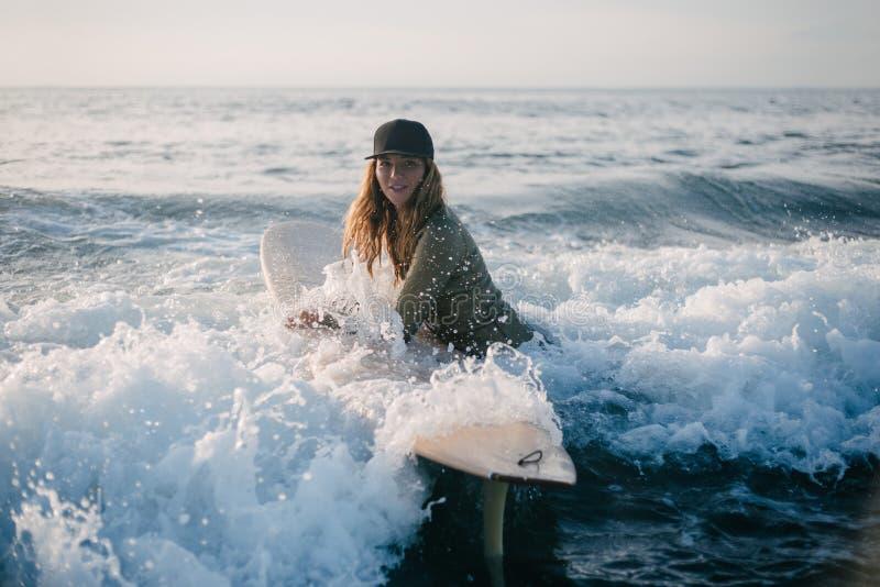 jeune femme dans le wetsuit avec la planche de surf entrant dans l'océan image stock