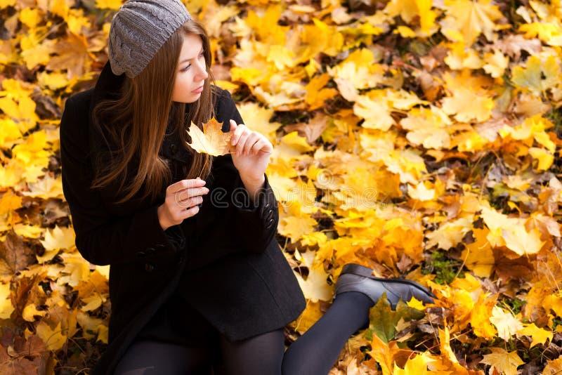 Jeune femme dans les couleurs vibrantes d'automne de stationnement image libre de droits