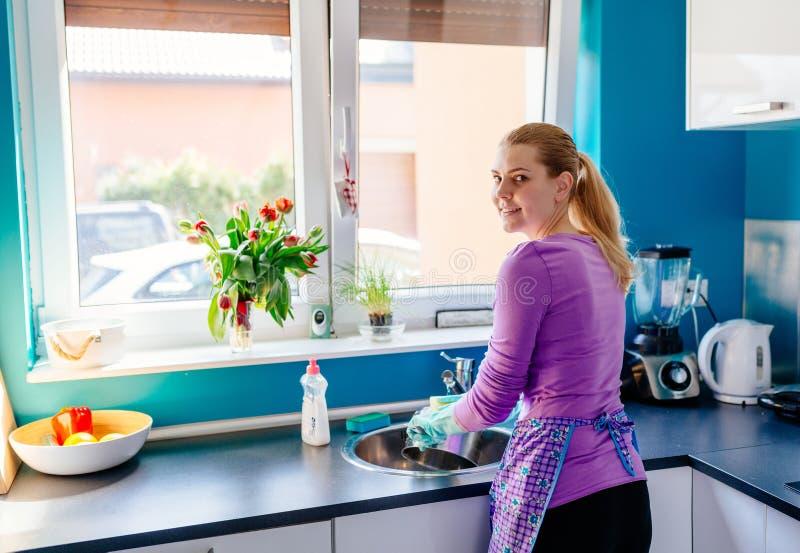 Jeune femme dans les gants en caoutchouc lavant des plats image libre de droits