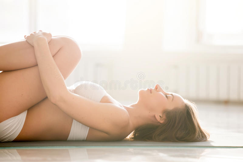 Jeune femme dans les genoux à la pose de coffre, fond blanc, plan rapproché images stock