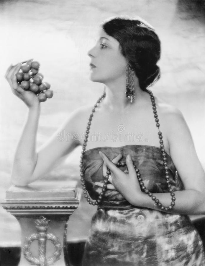 Jeune femme dans les perles et la robe élégante tenant et regardant des raisins (toutes les personnes représentées ne sont pas pl image libre de droits