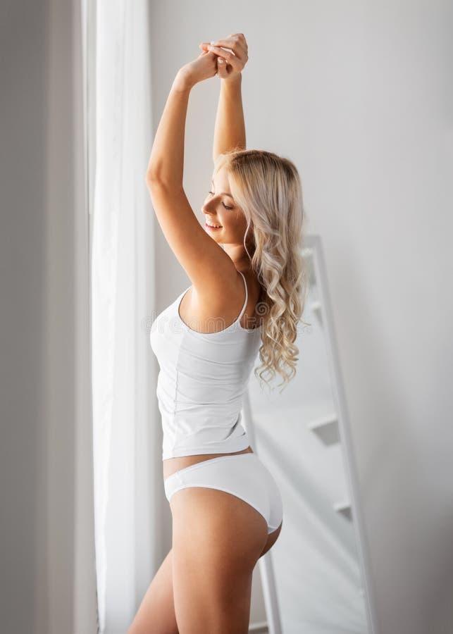 Jeune femme dans les sous-vêtements étirant à la maison la fenêtre images stock