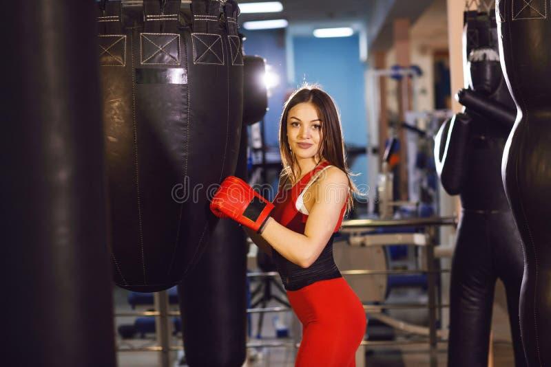 Jeune femme dans les vêtements de sports et les gants de boxe rouges, trains avec une poire de boxe dans un gymnase foncé images stock