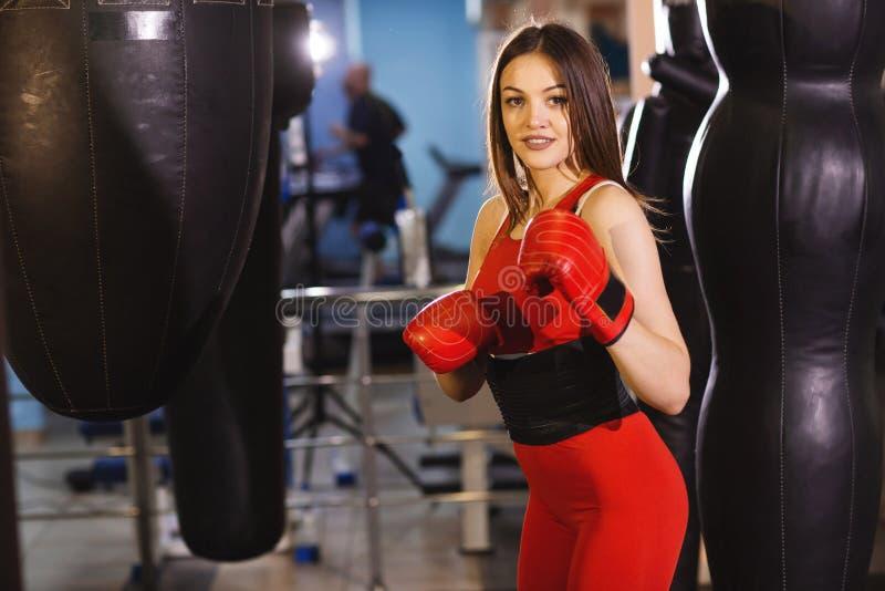 Jeune femme dans les vêtements de sports et les gants de boxe rouges, trains avec une poire de boxe dans un gymnase foncé photos stock