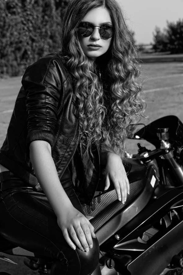 Jeune femme dans les vêtements et des lunettes de soleil en cuir près d'une moto Pékin, photo noire et blanche de la Chine photographie stock libre de droits