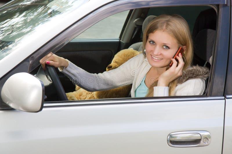 Jeune femme dans son véhicule tandis que sur le téléphone portable photographie stock libre de droits