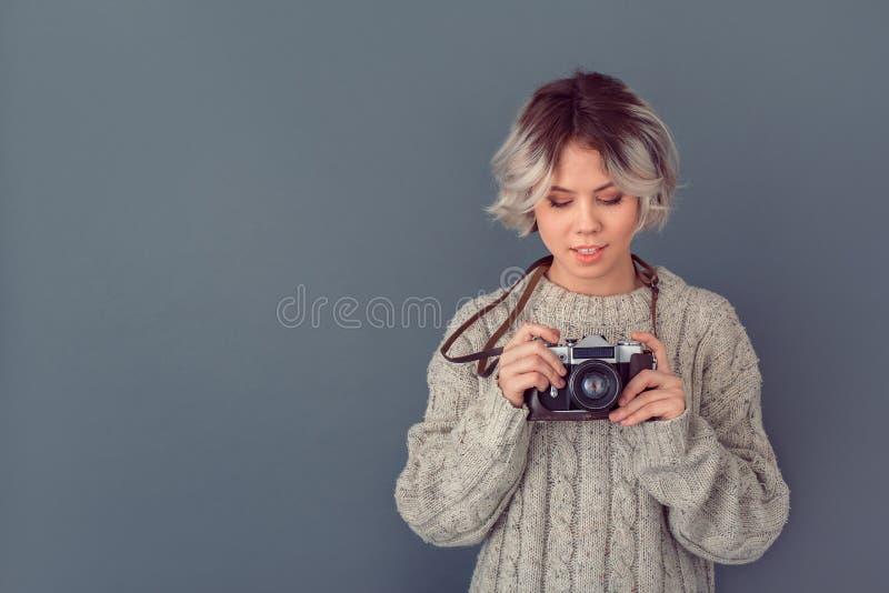Jeune femme dans un chandail de laine d'isolement sur le bouton gris de puissance de concept d'hiver de mur image stock