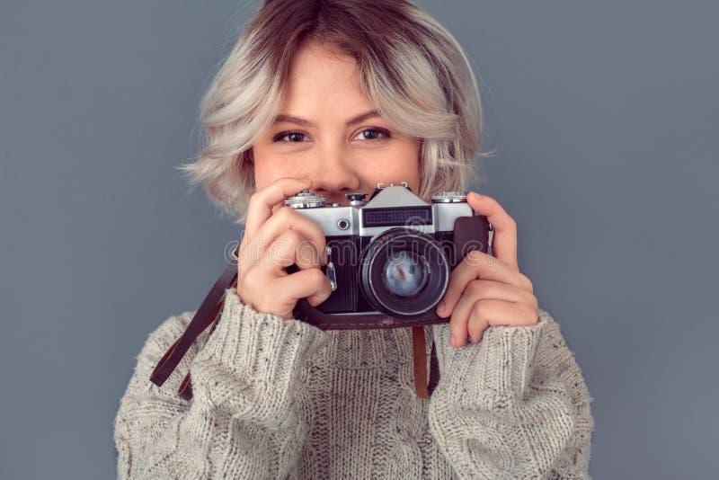 Jeune femme dans un chandail de laine d'isolement sur le concept gris d'hiver de mur tenant le sourire d'appareil-photo photo stock